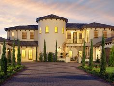 This expansive Mediterranean home has an arched front door and round tower entrance. The courtyard is planted with groupings of Italian cypress trees.