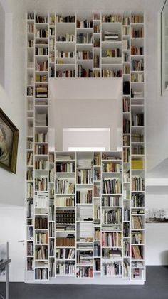 a double-height bookcase connects the upstairs to the downstairs through the atrium of this energy-efficient home in Hamburg... by Kraus Schoenberg Architects