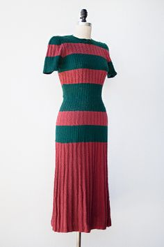 Made from a hunter green and raspberry colored cotton knit, this vintage 1930s / 1940s dress has short sleeves and a pleated skirt. The top 3/4 of the dress is stripped, with the largest stripe at the waist, which has a slimming effect.  Via Adore Vintage.