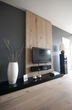 Like grey wall. Wood bhide tv. Black self White vase