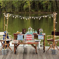 Lakeside picnic with make shift party lights perched in galvanized buckets, camp chairs, casual linens, and beautiful glass cloches on the table...charming.