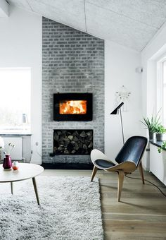 Cozy reading corner by the fireplace - enjoy a good book in the designer chair from Wegner.