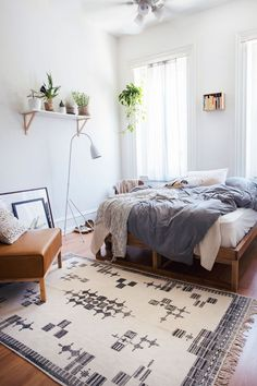 Urban and cool bedroom in warm tones featuring green plants and soft textiles.