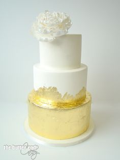 White and gold wedding cake with 24 karat gold leaf and signature white sugar flower by The Butter End Cakery
