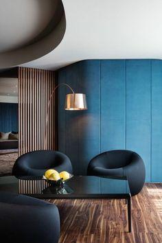 salon de luxe amenagement salon avec des fauteuils poufs en noir, faux plafond en niveaux différents, table rectangulaire noire avec pot aux fruits jaunes dedans, parquet en nuances beiges et marrons, luminaire sur pied incliné en couleur or, séparateur d'espace en bois clair, aux motifs rayures fines