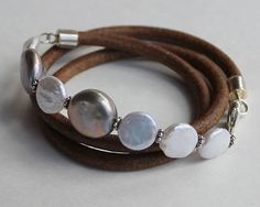 Pearl and Leather Stacking Bracelets multi by ChickpeaDesignStudio, $49.00 ETSY Triple wrap Pearl and Leather bracelet with silver and cream freshwater coin pearls, 6mm natural leather cord sterling end caps, closes with a sterling silver lobster clasp. Paired with a duo of stretchy pearl bracelets in creamy white and peacock black. 21 inch length plus stretchable 7 inch single strands