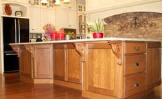 Custom Cupboards Cabinetry, custom hood with spice pullouts, Desert Cream finish on perimeter, enkeboll corbels and keystone, Fruitwood with Burgandy finish on island, Heartland door, Jeffrey Alexander hardware, mullion glass transom cabinets, wood appliance panels for Refrigerator, by Kitchen Sales Knoxville TN