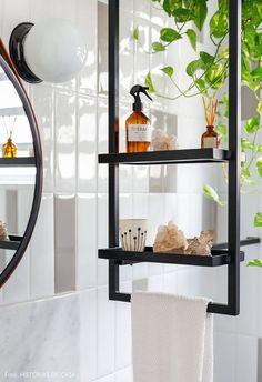 Banheiro com estilo industrial tem prateleiras de serralheria com plantas, cristais e aromatizadores.