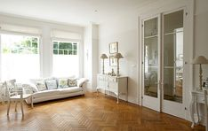 SHOOTFACTORY - WHITE SHABBY CHIC LIVING ROOM WITH WOODEN PARQUET FLOORING AND DOUBLE GLAZED DOORS LEADING TO HALL.