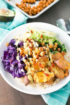 Spicy Buddha Bowl loaded with Brown Rice, Maple Sriracha Chickpeas, Roasted Sweet Potato, Veggies and a creamy Turmeric Tahini Dressing. Vegan | Gluten Free