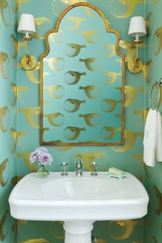 In a Florida Gulf-front home, gilded puffer fish swim past brassy sconces and an antiqued bronze mirror for a sophisticated take on underwater style.