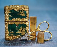 VERY FINE FRENCH ENAMELED NECESSAIRE WITH CHINOISERIE DESIGNS AND GOLD SEWING TOOLS The heavy necessaire has rich emerald green enamel finish that is decorated with hand-painted gold Chinoiserie designs including castle scenes with waving flags,and has richly-sculpted gold ormolu frame.Gold-handled folding scissors with silver blades,gold needle holder and a petite gold thimble with alternating vertical bands of plain,geometric and floral designs. French,circa 1860