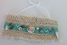 item #B083-SS The blue crush wrap- is made of coral, turquoise, mini-sea shells, pukas and a large spiral shell all sewn on a selection of laces- with adjustable faux suede cords.