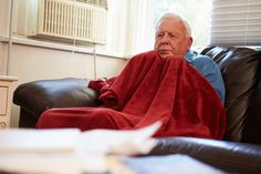 Senior Man Trying To Keep Warm Under Blanket At Home