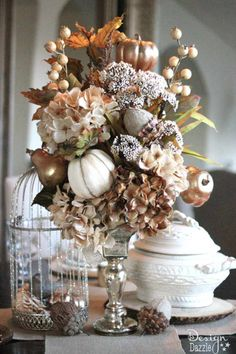 For a breathtaking Thanksgiving centerpiece, use muted yet elegant colors in your tablescape that features an assortment of faux fall foliage.