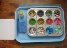 A mini muffin tin is filled with fun small materials, a paintbrush and bottle of glue to be used to create a collage.