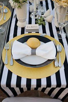chemin de table aux rayures blanc-noir, assiettes jaunes-noirs, table en bois