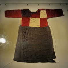 SECRETS OF SILK ROAD Pull over skirted dress.  5th to 3rd century BC.  This child's pullover skirted dress was made from a patchwork of multicolored wool pieces.  On the ends of the long sleeves and hem, triangular pieces of wool have been added to increase the length of the garment.  This is one example of the many kinds of woolen garments of different weaves and quality that have been found in the Zaghunluq tombs.
