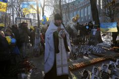 An Orthodox priest leads a service at a memorial dedicated to people who died in clashes with security forces in Kiev, Wednesday, Feb. 18, 2015. Municipal workers are preparing the square to commemorate the Maidan protest movement and the events which took place in late Feb. 2014 that led to the departure of former Ukrainian President Victor Yanukovich and the formation of a new government.