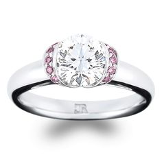 "Pretty in pink. ""Charme"" features 10 fine pink brilliant cut diamonds, surrounding a round brilliant cut centre. This fully hand-made setting is available in 18"