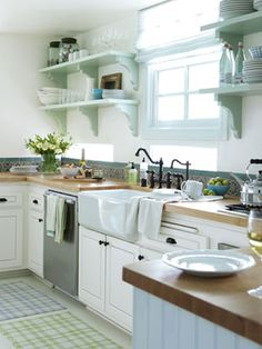 To give the kitchen a sense of lightness, Angle removed upper cabinetry and replaced it with open shelves, painted Farrow & Ball's Teresa's Green.