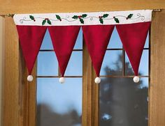 Post-Xmas raid-the-sales: Dollar Santa hats become a valance for a Christmas retail display window : make a hole on two sides of each Santa hat, thread onto curtain or tension rod. Done!