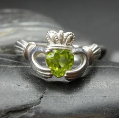 Heart shape Peridot Claddagh ring. I have an all-silver one of these that needs refitting but I'd never seen one with a stone! A peridot no less! <3