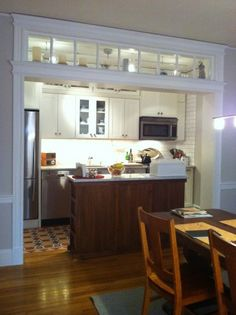 White kitchen cabinets in the Rockford door style from CliqStudios. The cozy kitchen features a nicely contrasting island, prepped for glass doors, and cabinets that extend to the ceiling for added storage.