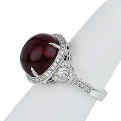 This stunning ring features an antique look with milgrain work on the 18kt white gold band. The center stone is 15.92 carat cabochon ruby. There are also brilliant diamonds with a total weight of .97 carats.
