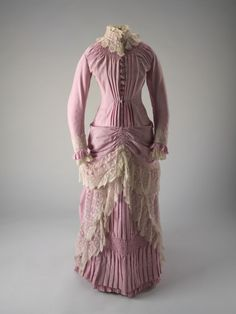 This 1885 dress shows how gowns in the middle of the era might have looked. The dresses began to hug the body closer and the volume moved to the bottom of the dress.