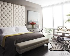 A floor-to-ceiling tufted headboard looks almost subdued when displayed against a soft gray wall. Was the paint color inspired by the family poodle?      Source: Photography by Bjorn Wallander for Elle Decor