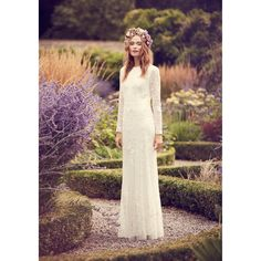 This bridal dress from the 'Nine' collection by Savannah Miller exudes timeless elegance and showcases a touch of bohemian charm. Draping to a beautiful floor-length, it features mesh sleeves and exquisite lace detailing adorned with sequin embellishments for a shimmering finish.
