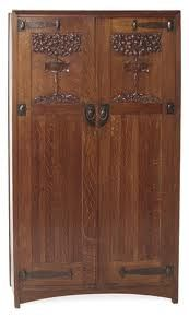 Arts and Crafts Wardrobe. Carved Oak with Brass Hardware. England. Circa 1900.
