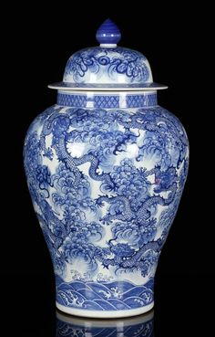 """Later 19th century Chinese blue and white jar, porcelain, with lid, decorated with dragons amongst clouds over waves, 23"""" h."""