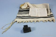 Auschwitz - Jewish prayer book, a tallit - Jewish prayer shaw and a tefillin - small cubic leather box painted black, containing scrolls of parchment inscribed with verses from the Torah, worn by observant Jewish men during weekday morning prayers.