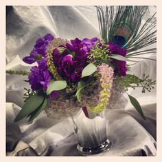 Peacock feathers add an elegant touch to this centerpiece. (Flowers designed by Seven Sisters Florist) www.sevensistersflorist.com