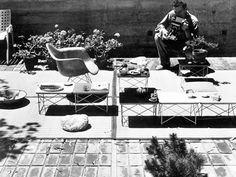 Charles photographing the Wire Base Low Table on the patio of the Eames House, 1951