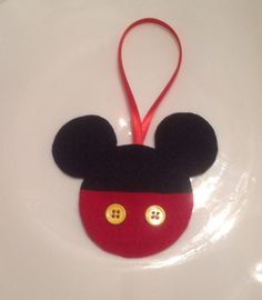 Easy felt ornament. Trace Mickey head on felt...cut out. Take red felt, trace and cut out bottom. Glue red on black, glue yellow or white buttons on. Glue ribbon on back.