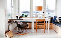 """Kökssoffan i plywood har Emma byggt själv. En klassiker dyker även upp här: Ray och Charles Eames """"Rockin' chair"""". Kopparna på bordet är gjorda av formgivaren Anna Lerinder. Taklampan """"Nagoia"""" är från 60-talet, design Ferran Freixa för Santa and Cole. Den rutiga kudden är klädd med Emmas tyg """"Domino""""."""