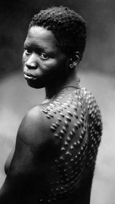 Africa | Karamojong woman with scarification. | Picture taken in the 30s this young girl was posing in the French West Africa (AOF).