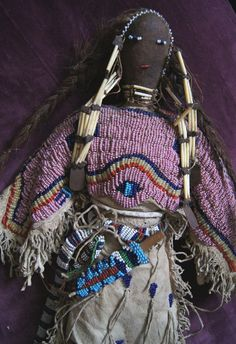 "Lakota Beaded and Quilled Doll 1880-1890A from the early Reservation period, possibly Pine Ridge Agency. With a fully beaded yoke with morning stars and ""turtle emerging from the lake"" motif in predominately Cheyenne pink, cobalt blue ""tadpoles"" with fringe and three band bottom trim on a fully fringed old pattern hide dress made of Native tanned antelope hide..."
