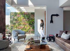 Living | A moradora Alessandra Passos caminha até o jardim vertical da By Floor, que tem status de obra de arte no estar. Poltrona Gioconda, revestida de lona de caminhão, e sofá de couro desgastado, da Vivence Interiores (Foto: MCA Estúdio)