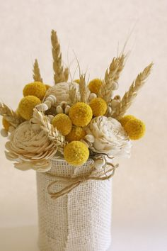 An upcycled tin can wrapped with white burlap and accented with a natural twine has been filled with craspedia, sola roses, tallow berries, and rye