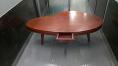 Mid Century, Noguchi style kidney shaped three-leg wood coffee table with center draw. In great shape.