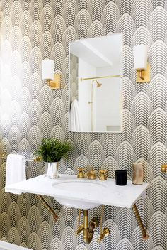 Black and white wallpaper in bathroom with gold sconces and exposed gold hardware.