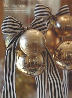 A mix of glossy and matte Christmas ornaments in a cluster with chic black & white striped ribbon at the top
