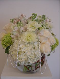 Short white and ivory centerpiece with pearl. Roses and pearls. - love the hanging pearl