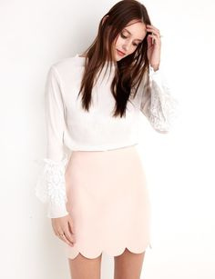 A pretty pastel pink mini skirt with a scalloped hemline.