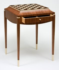 I like the idea of a chess table. Although looking at this design I wouldn't be able to incorporate the drawer and the curved top I can still use the features such as the thin tapered legs and the rails and also a chess board as the surface.