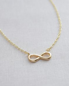 Infinity Necklace by Olive Yew. This pretty little infinity necklace is perfectly sized to give your outfit some shine. Available in gold and silver.